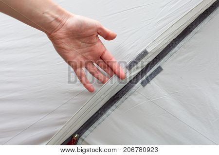 Girl hand unzip the entry of camping tent on rainfly