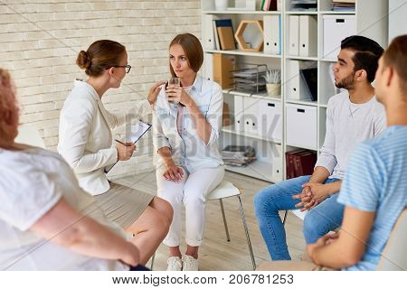 Portrait of  female psychiatrist consoling young woman suffering from depression during group therapy session