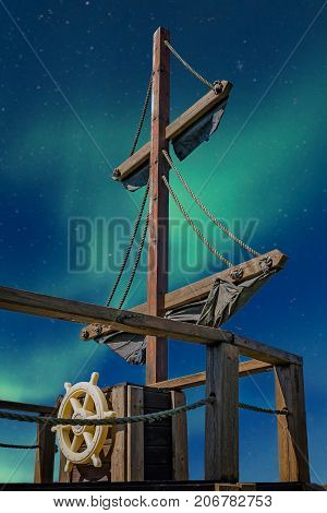 Deck of a pirate ship with mast and steering wheel with a aurora on a night sky in the background