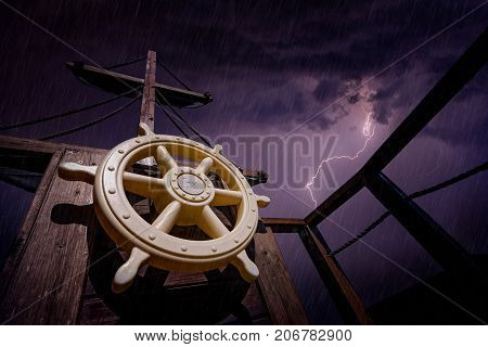 Steering wheel and wooden mast of a pirate ship during storm with stormy skies and lightening in the background