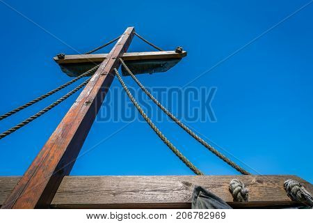 Mast of a pirate ship with midday sun shining over blue sky background