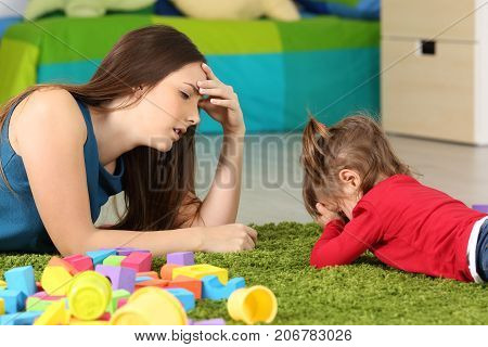 Angry baby and tired mother lying on a carpet in a room