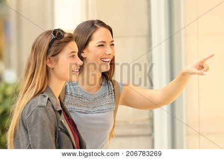 Two happy shoppers watching a storefront on the street
