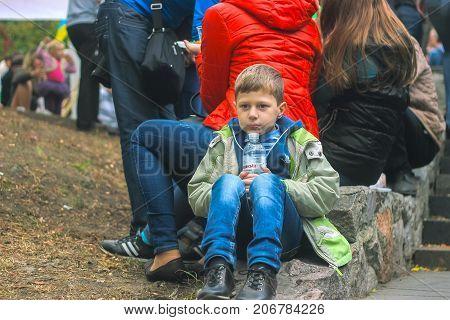 Zhytomyr Ukraine - September 05 2015: sad teen sit on the ground by holding bottle in hands at crowd