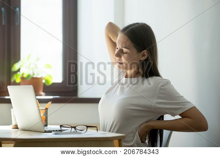 Female manager taking short break after long day of work on laptop computer. She took off her glasses, closed her eyes and stretching her aching back with a pained expression.