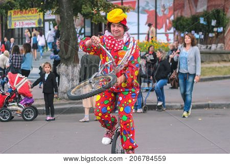 Zhytomyr Ukraine - September 05 2015: Clown jumping on unicycle at street in the evening