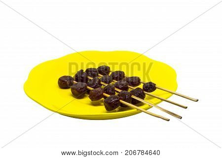 Caramelized Star gooseberry (Star gooseberry in syrup) and wood stick on yellow dish isolated on white background with clipping path. Close up of thai dessert in yellow plate.