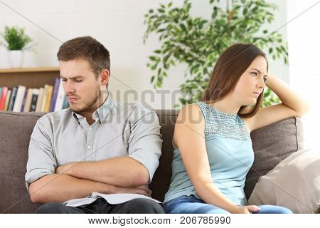 Angry couple ignoring each other after argument sitting on a sofa at home