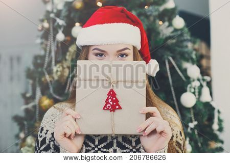 Young happy girl in red santa hat covering half face with christmas gift on xmas tree background. Funny and joyful winter holiday wallpaper