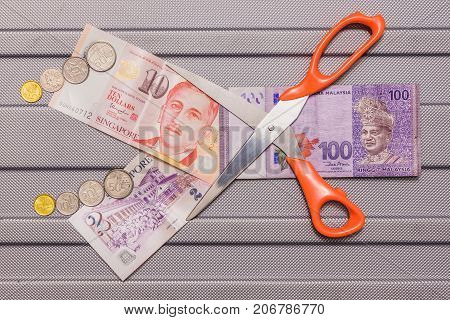 Singapore dollar and Coins on top of Malaysian Ringgit currency on pattern background Concept currency exchanges money value cutting down Malaysian Ringgit code is MYR Singapore Dollar is SGD