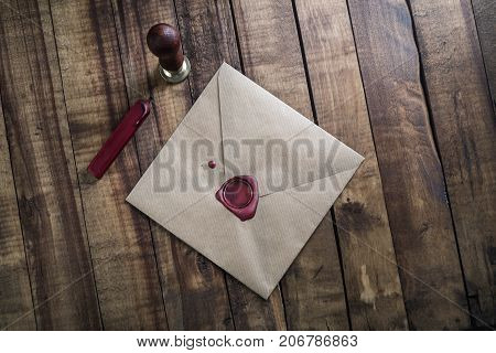 Blank vintage envelope sealing wax and stamp on wood table background. Responsive design mock up. Postal stationery. Top view.