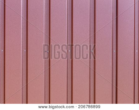 Reddish-brown metal fence made of corrugated steel sheet with vertical guides and metal rivets in the middle. Corrugated reddish-brown iron sheet background close up.