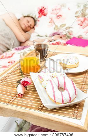 a woman sleeping in the bed with breakfast tray near her