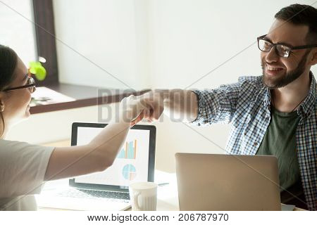 Celebrating job well done. Two businesspeople fist bumping in winning gesture, rising stats on their laptop.