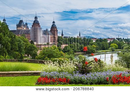 Beautiful view of the old town Aschaffenburg Germany and the palace Johannisburg on shore of river Main on the background of blue cloudy sky and green plants and flowers. Tourist attraction place of visiting tourists.