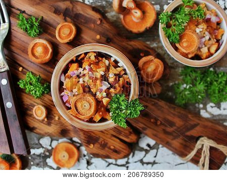 salad of fresh saffron milk caps with red onion and fresh parsley and whole mushrooms on a wooden Board