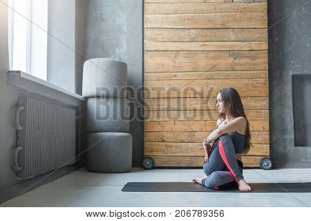Young woman in yoga class doing back stretching asana. Fit girl in ardha matsyendrasana. Healthy lifestyle in fitness club, copy space on wall