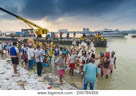 KOLKATA WEST BENGAL INDIA - 30 SEPTEMBER 2017: Idol of Goddess Durga is being immersed in Holy river Ganges. Celebrated by Hindus as