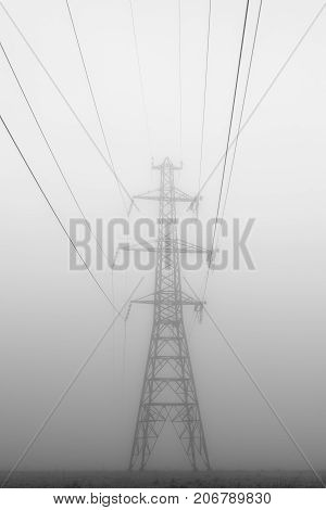 A tall power line tower looms in the fog.