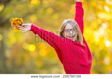 Happy Fall Girl Smiling And Joyful Holding Autumn Leaves. Beautiful Young Girl With Maple Leaves In