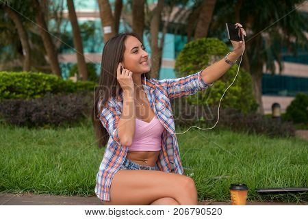 Happy young woman wearing headphones and taking a photo in the park sitting on the curb. Attractive female taking selfie