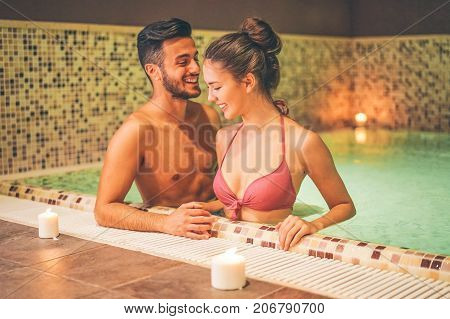 Happy couple relaxing in a warm pool hydromassage at hotel spa - Young lovers having fun in a thermal bath - Couple and wellbeing concept - Soft saturated editing - Focus on female face