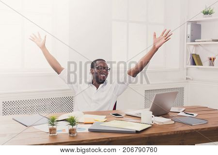 Happy excited businessman celebrate. Winner, black man in office with laptop