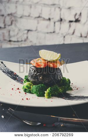 Excuisite restaurant food background. Dorado fillet wrapped in nori on broccoli pillow with shrimps and lemon piece on topnon white platter, sprinkled with pepper salt. Copy space on white brick wall