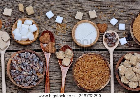 Variation sugar in a bowls and spoons on wooden table