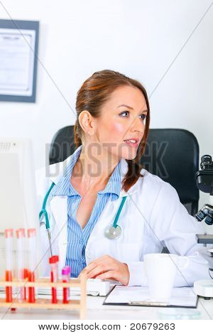 Medical doctor woman sitting at office table and looking away