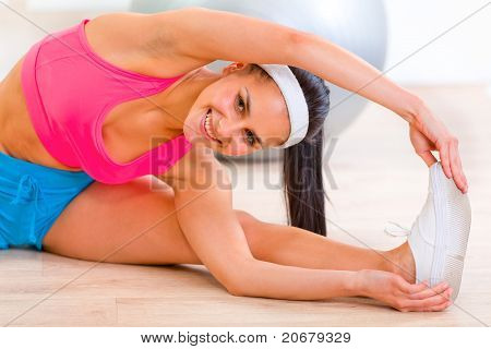 Smiling flexible young girl stretching legs on floor at living room