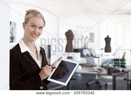 Entrepreneur in small business - young and ambitious business entrepreneur in fashion design studio using tablet.