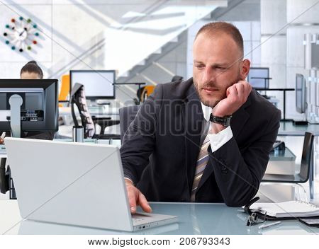 Confident caucasian stock broker working at bright financial business office desk with laptop computer. Determined, suit. poster