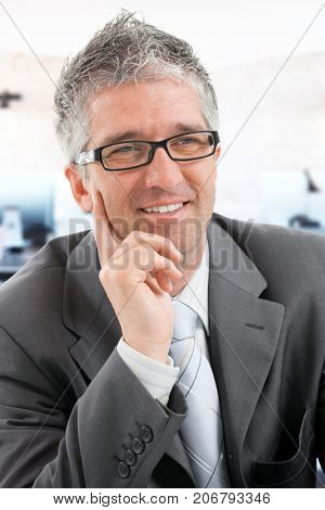 Portrait of confident businessman leaning on elbow, smiling.