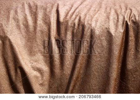 The folds of the old brown embroidered fabric