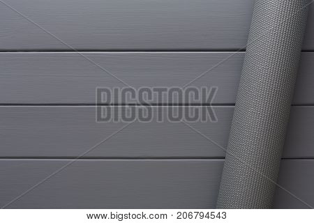 Pilates background. Rolled up yoga mat for exercise on grey wooden floor. Sport class before or after practicing yoga, preparing for exercise, top view, copy space