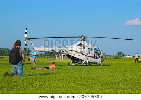Zhytomyr Ukraine - May 05 2015: Young Man Sunbathing at helicopter starting competition while him shooting on camera