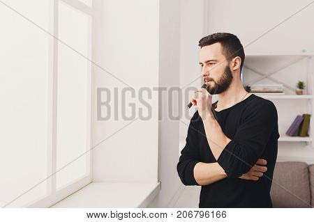 Confident young bearded man vaping electronic cigarette standing against the window on white background. Nicotine free smoking and vapor concept, copy space