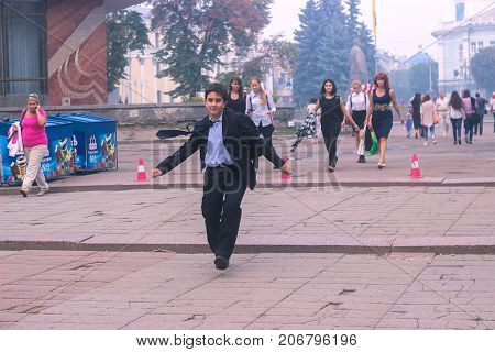 Zhytomyr Ukraine - October 03 2015: Happy schoolboy with his school bag on his shoulders running on a sunny day. Child going home from school. Cute boy rushing.