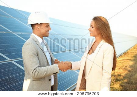 Engineer and client shaking hands after discussion of project on solar panels installation outdoors