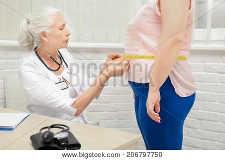 Elderly doctor measuring waist of overweight woman in hospital