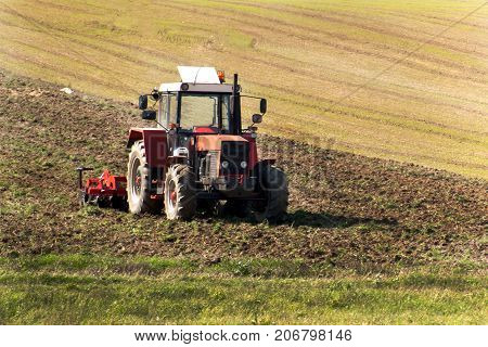 Red tractor in the field. Agricultural farm work. Agriculture in the Czech Republic