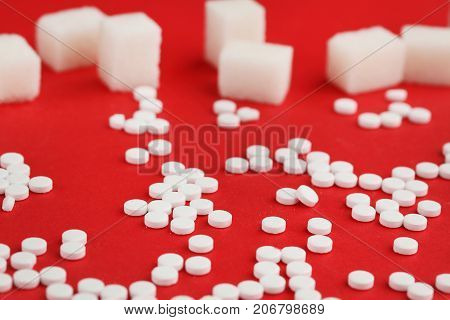Sweetener Tablets And Sugar Cubes On Red Background