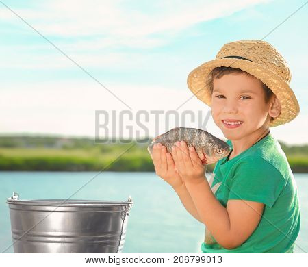 Cute little fisher with catch on summer day
