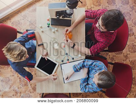 Stem education. Teenagers studying at biology lesson in laboratory, sitting with equipment, using gadget and blank notebook, top view, copy space
