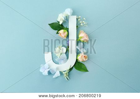Composition with letter J and beautiful flowers on color background