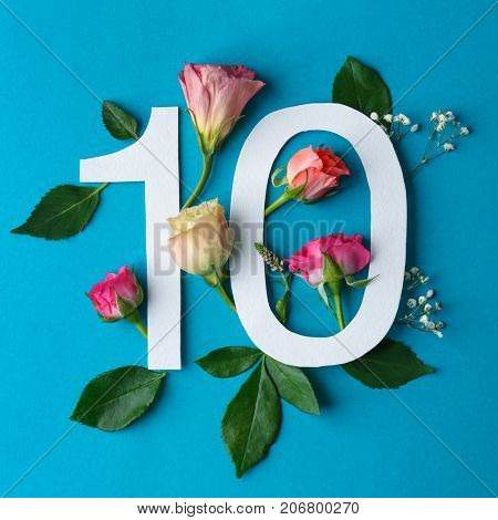 Composition with number 10 and beautiful flowers on color background