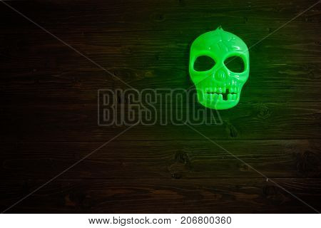 Halloween Glowing Phosphoric Human Skull Over Wooden Table Background. Neon Light