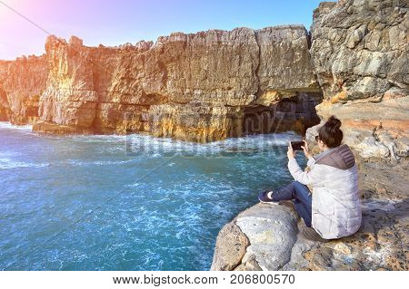 Young Woman taking pictures on a mobile phone of cave The Devil's Mouth, Portugal
