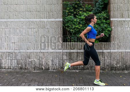 Profile view of a sporty young woman working out outdoors. Fitness girl running on sidewalk